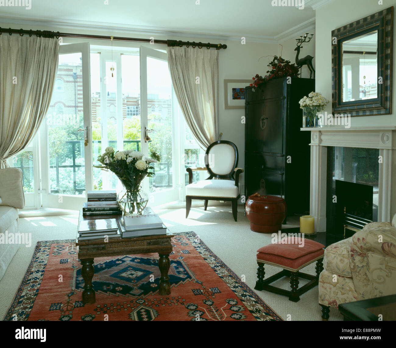 Coffee Table On Red Oriental Rug In Apartment Living Room With Open French  Doors To Balcony With View Of The City