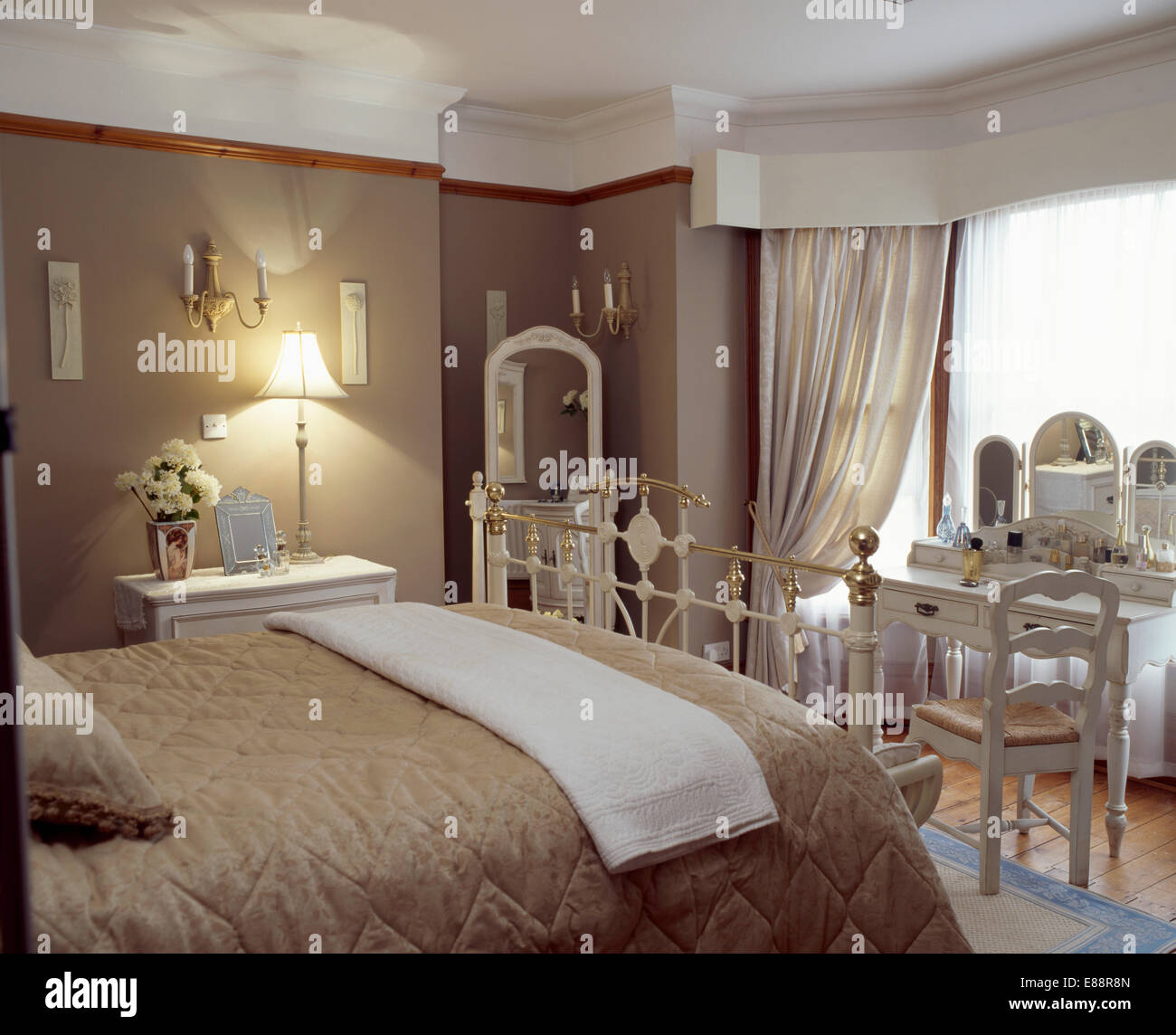 cream throw and dark beige quilt on brass bed in beige bedroom with lighted lamp and window with cream curtains - Beige Bedroom