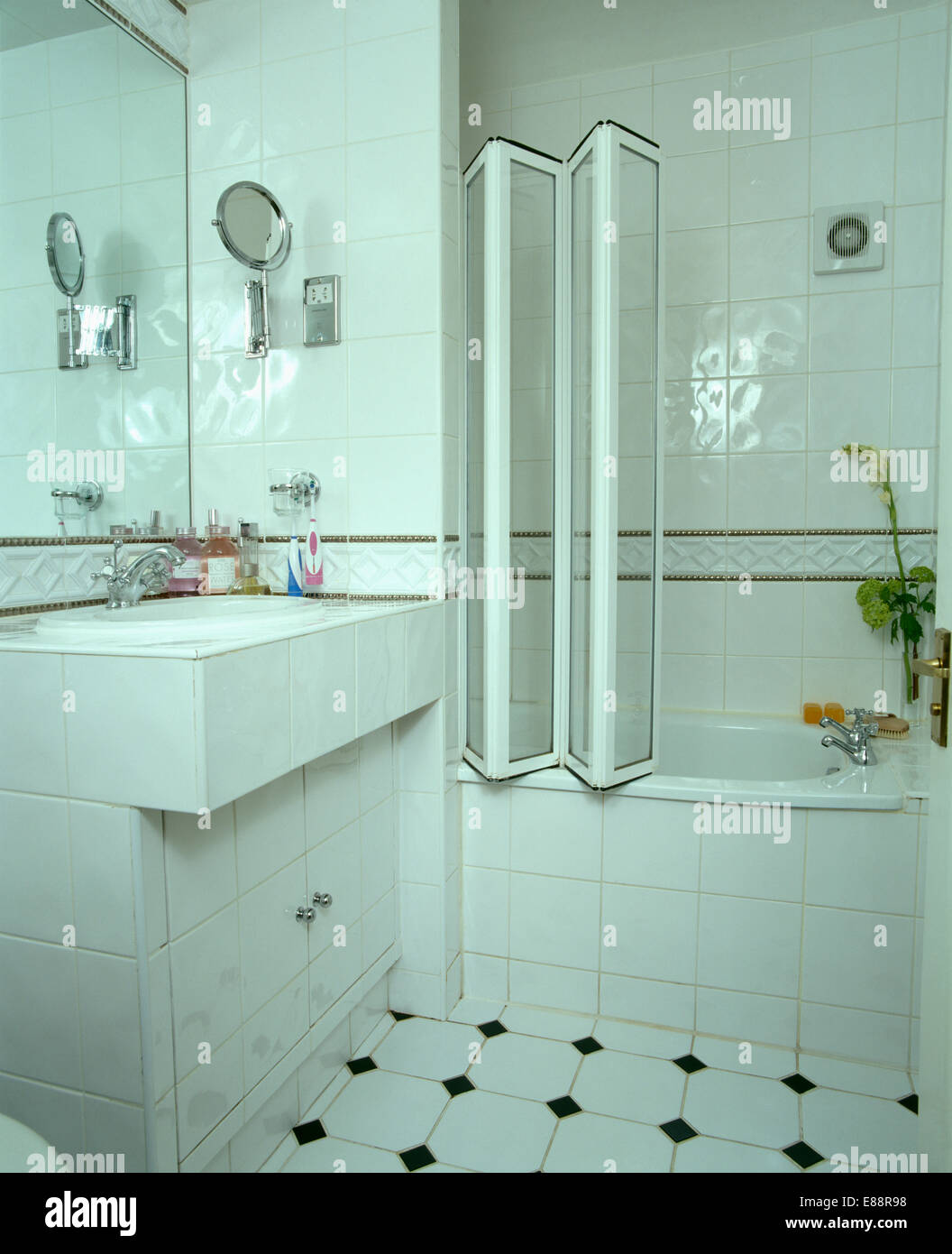 Folding glass shower doors on bath in modern white tiled bathroom ...