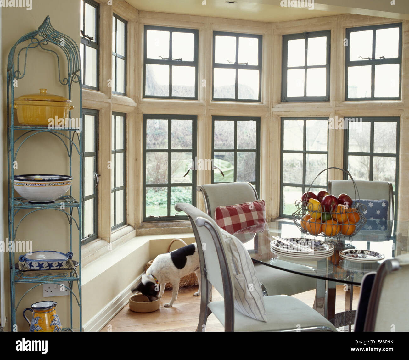 Narrow metal shelving beside large bay window in country dining ...