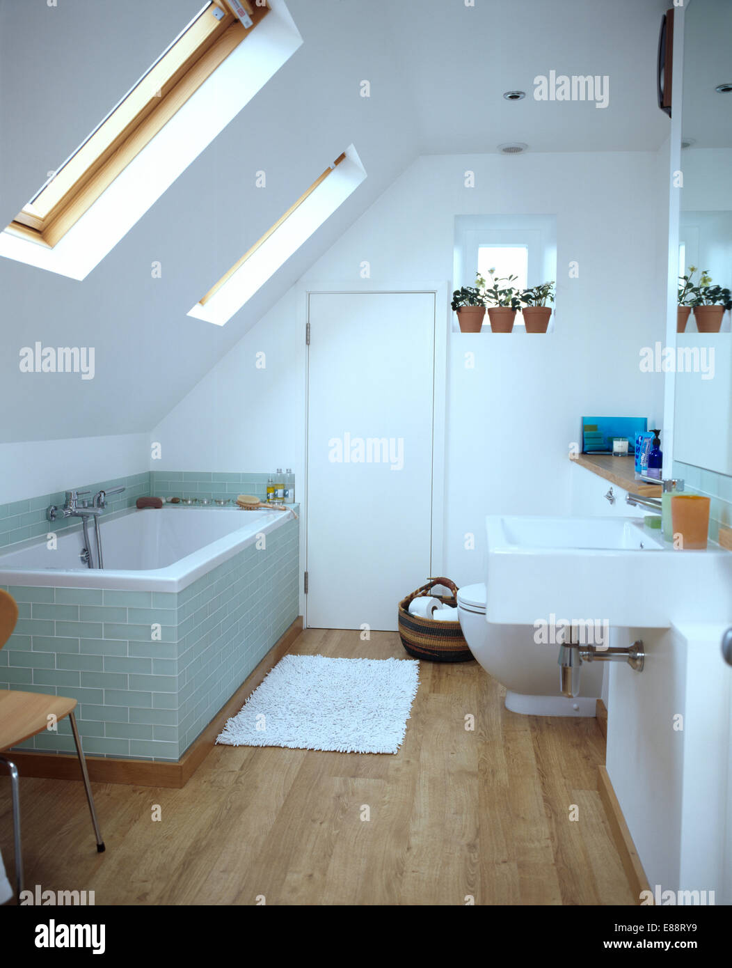 Glass tiled surround on bath in modern white loft conversion ...