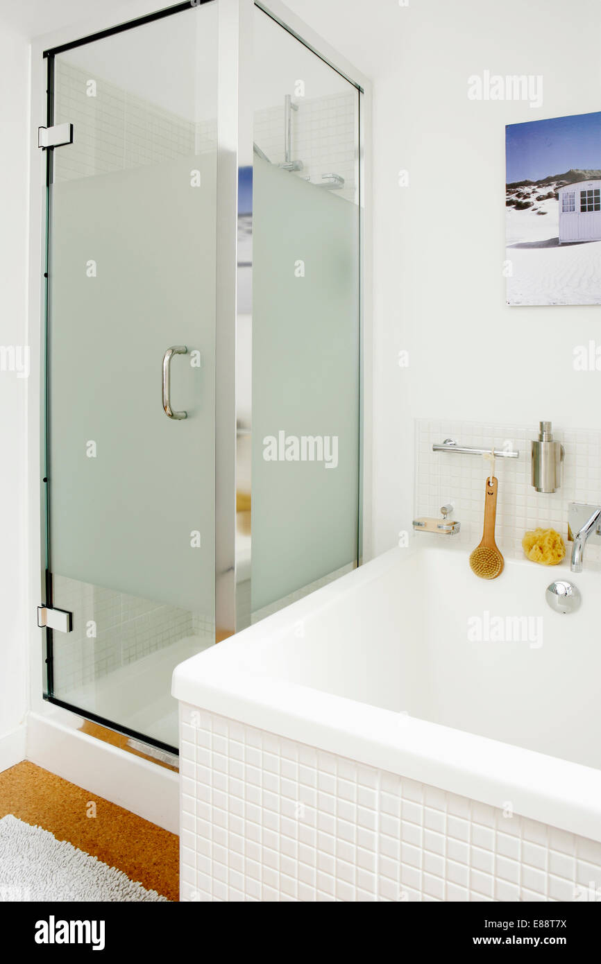 Glass shower cabinet beside bath with white mosaic tiled surround in ...