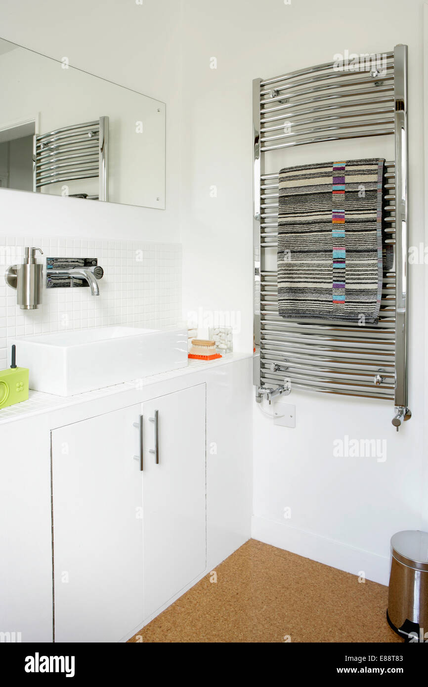 Chrome heated towel rail on wall in modern whtie bathroom with Stock ...