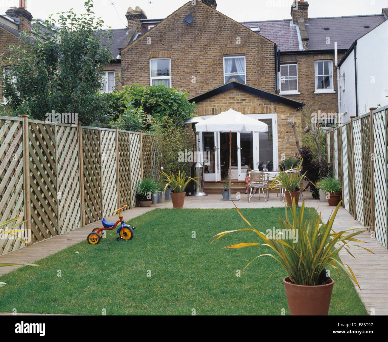 Lawn and trellis fence in back garden of townhouse with small Stock