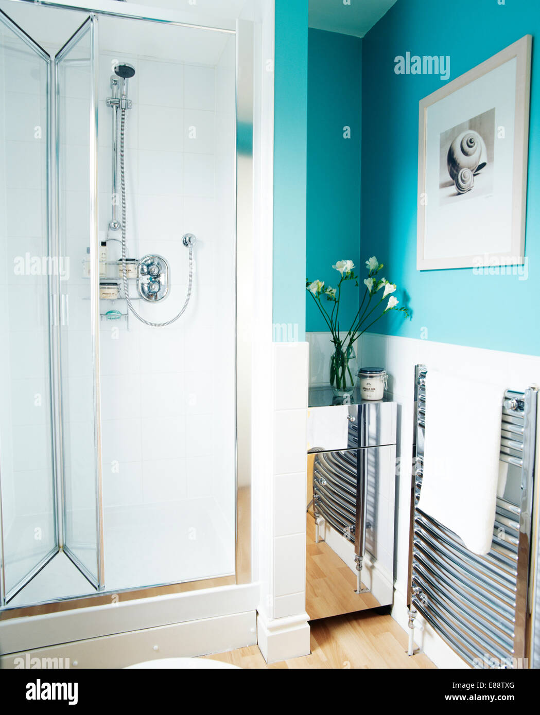 Folding glass door on shower cabinet in modern turquoise bathroom ...