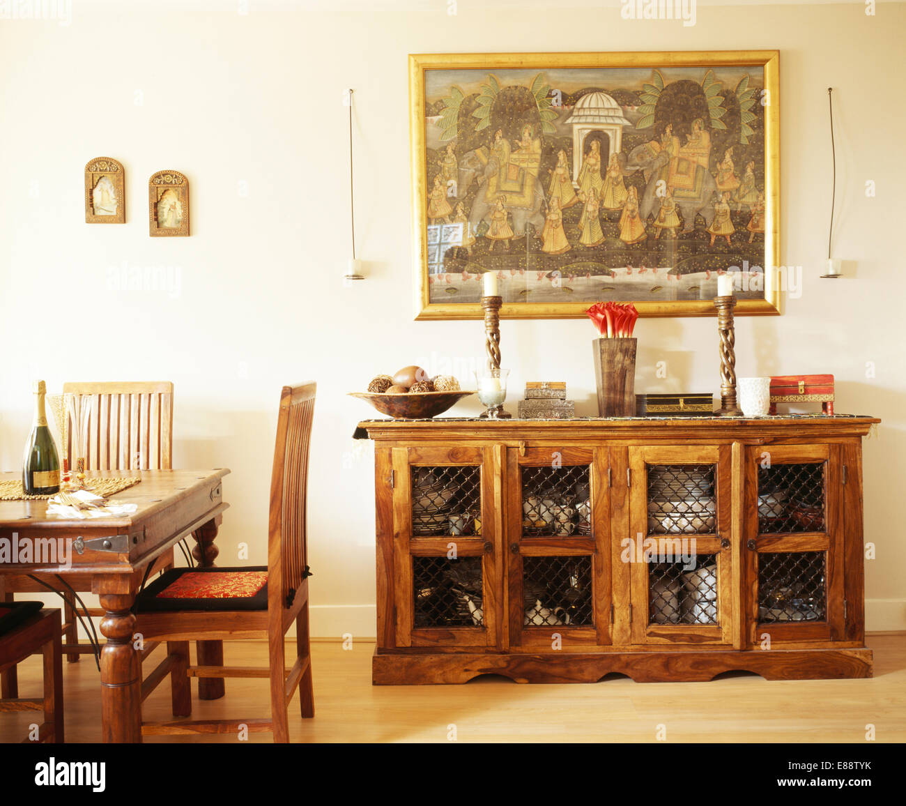 Large Indian painting above rustic wood sideboard in modern dining room - Stock Image