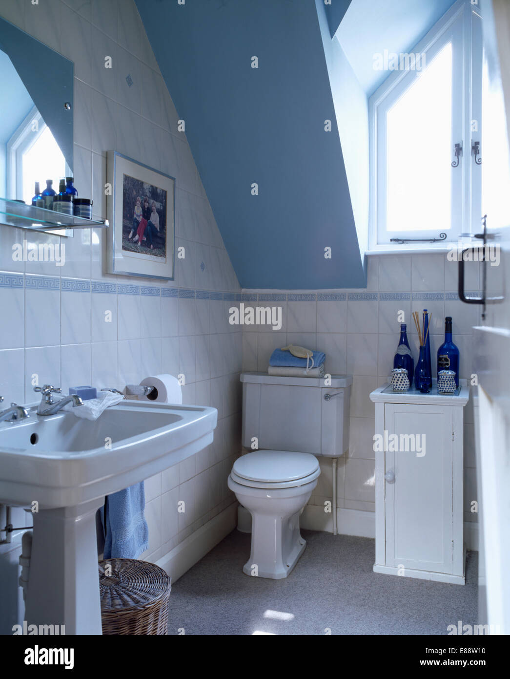 White pedestal basin and toilet in blue attic bathroom with small ...