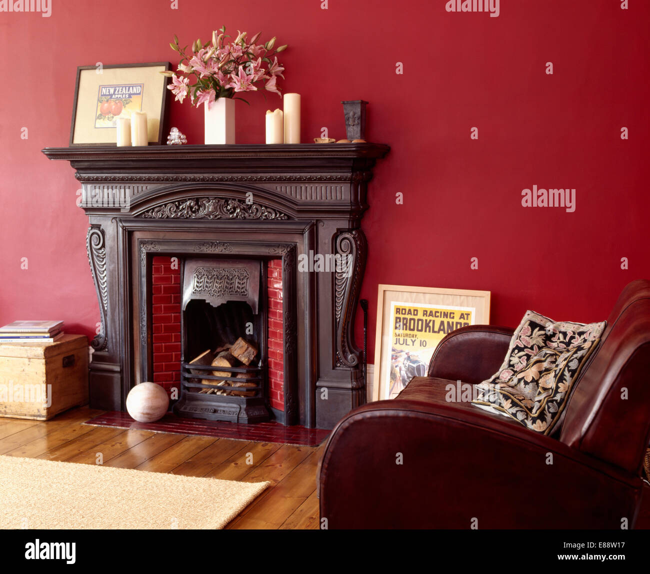 Black cast-iron fireplace in red living room with brown ...