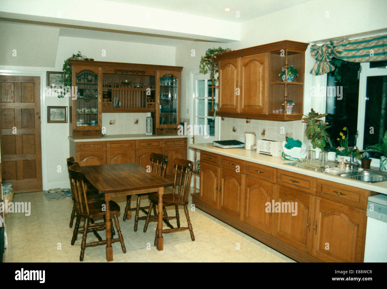 Wooden table and chairs in old-fashioned eighties kitchen before renovation - Stock Image
