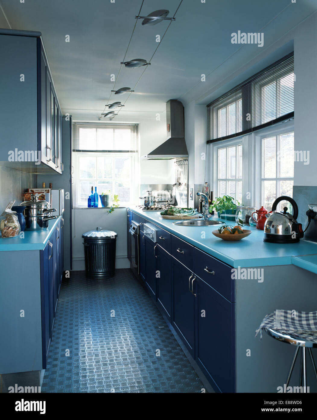 Rubber Flooring In Modern Galley Kitchen With Pale Blue Worktops And  Stainless Steel Waste Bin