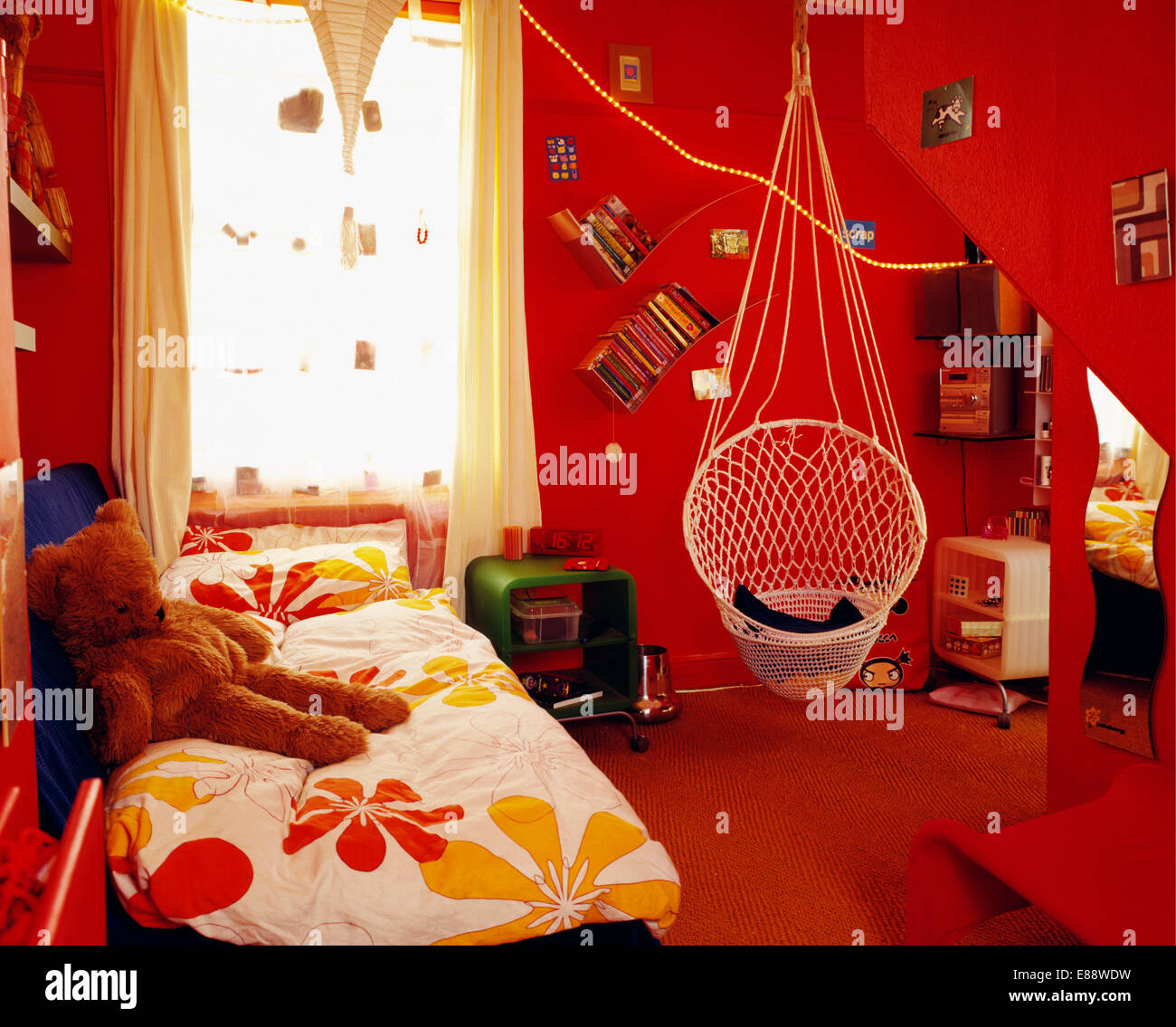 Stylised-floral patterned duvet on bed in teenager's red bedroom with cane chair suspended from the ceiling - Stock Image