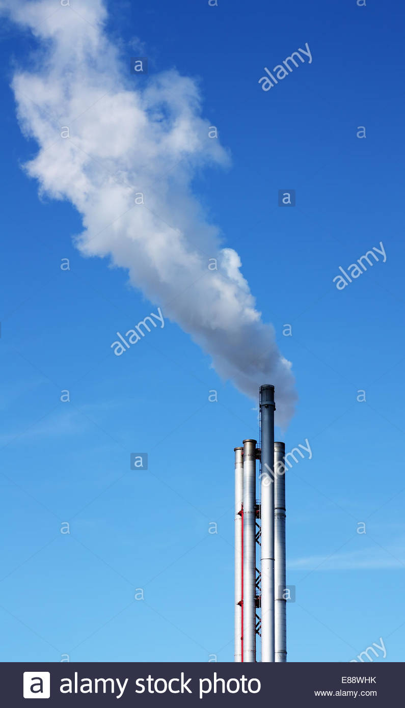 Chimneys in an industrial area exhausting smoke. - Stock Image