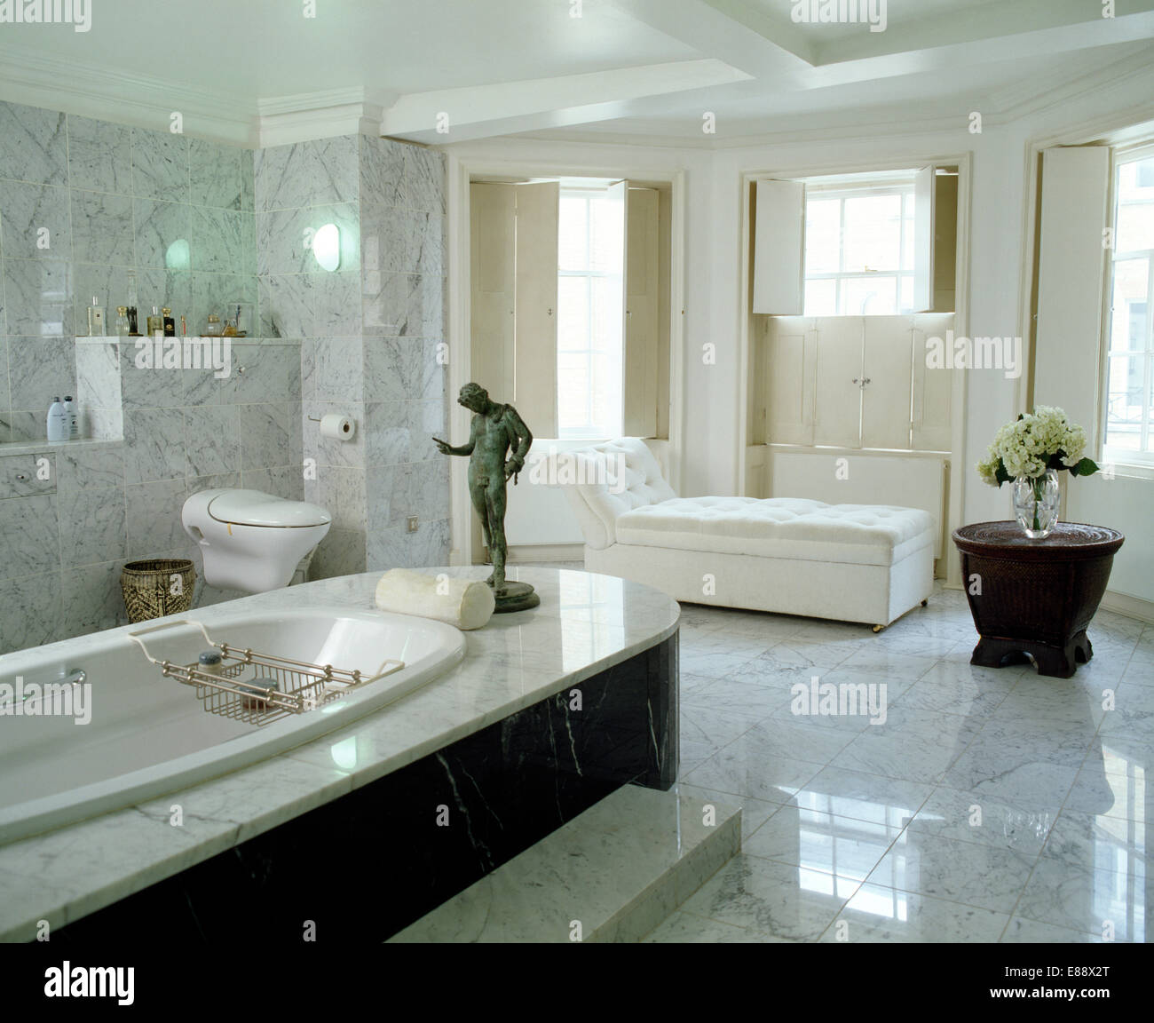 Bronze Classical Statue On Marble Panelled Bath In Pale Grey Marble Bathroom  With Marble Flooring