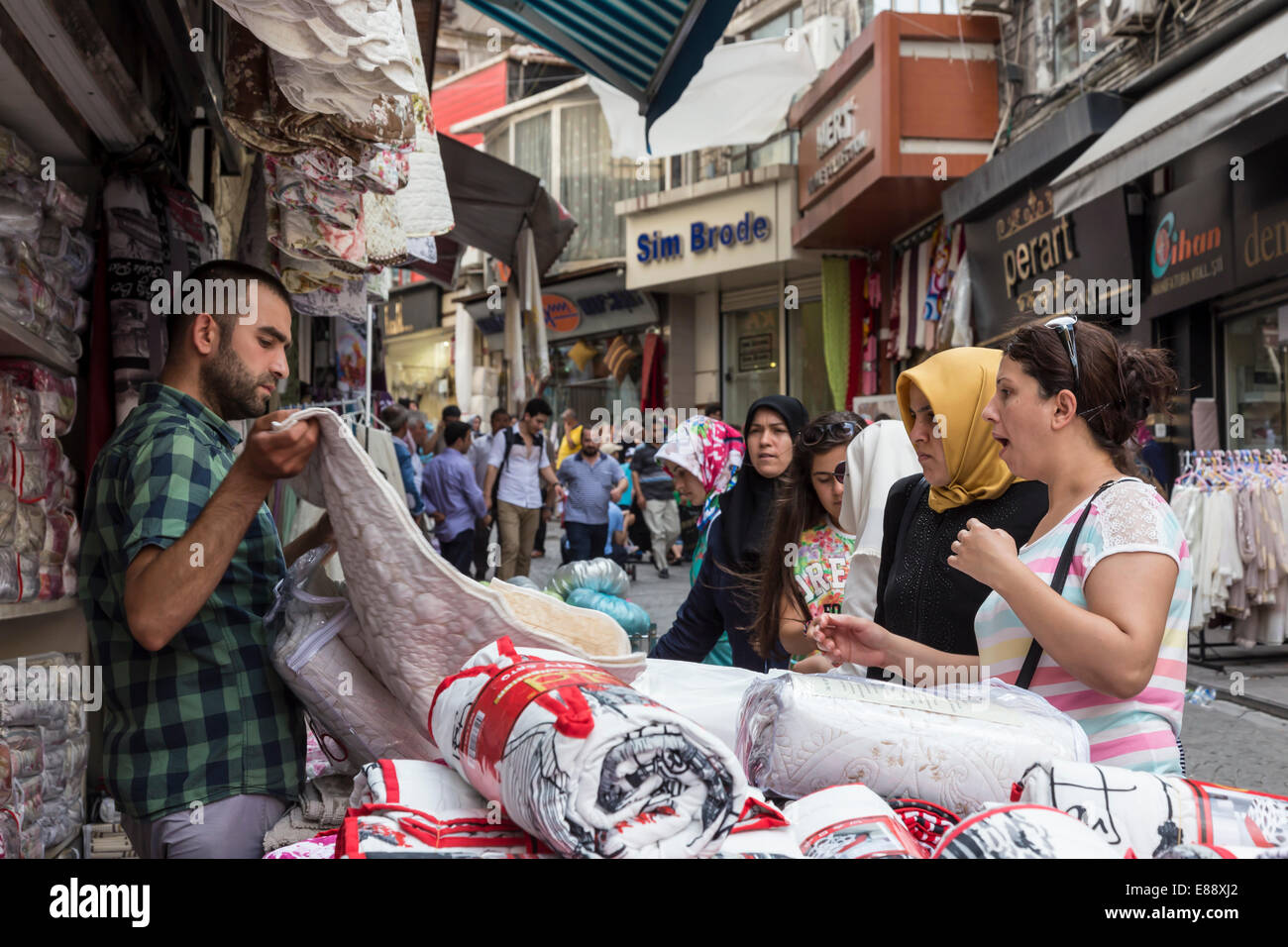 Turkish women making a bargain with a vendor (seller), street linking Grand and Spice Bazaars, Bazaar District, - Stock Image