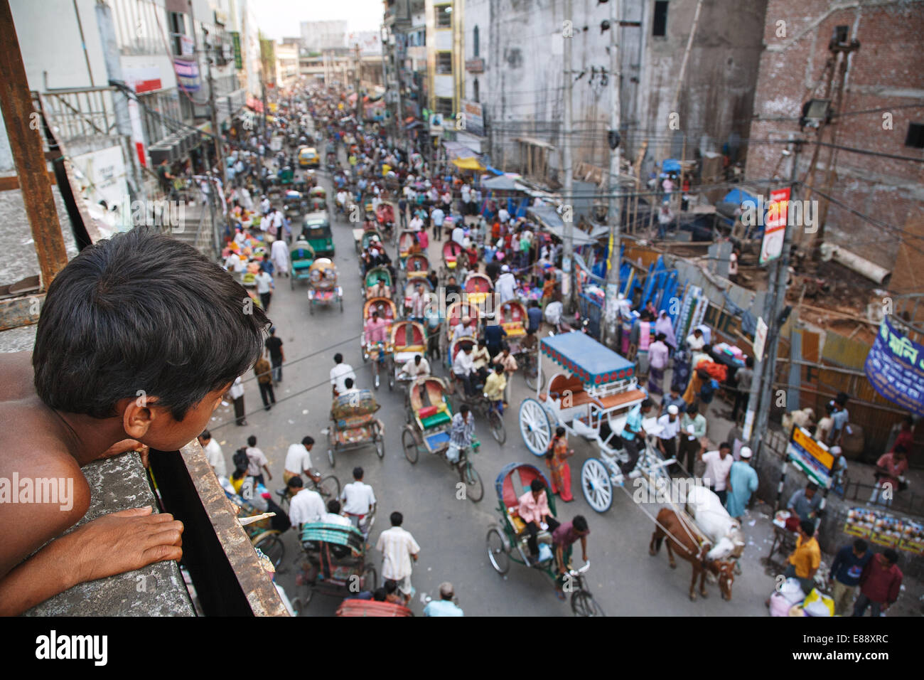 A boy watches road traffic with rickshaws on the main road in the Old City of Dhaka, Bangladesh - Stock Image