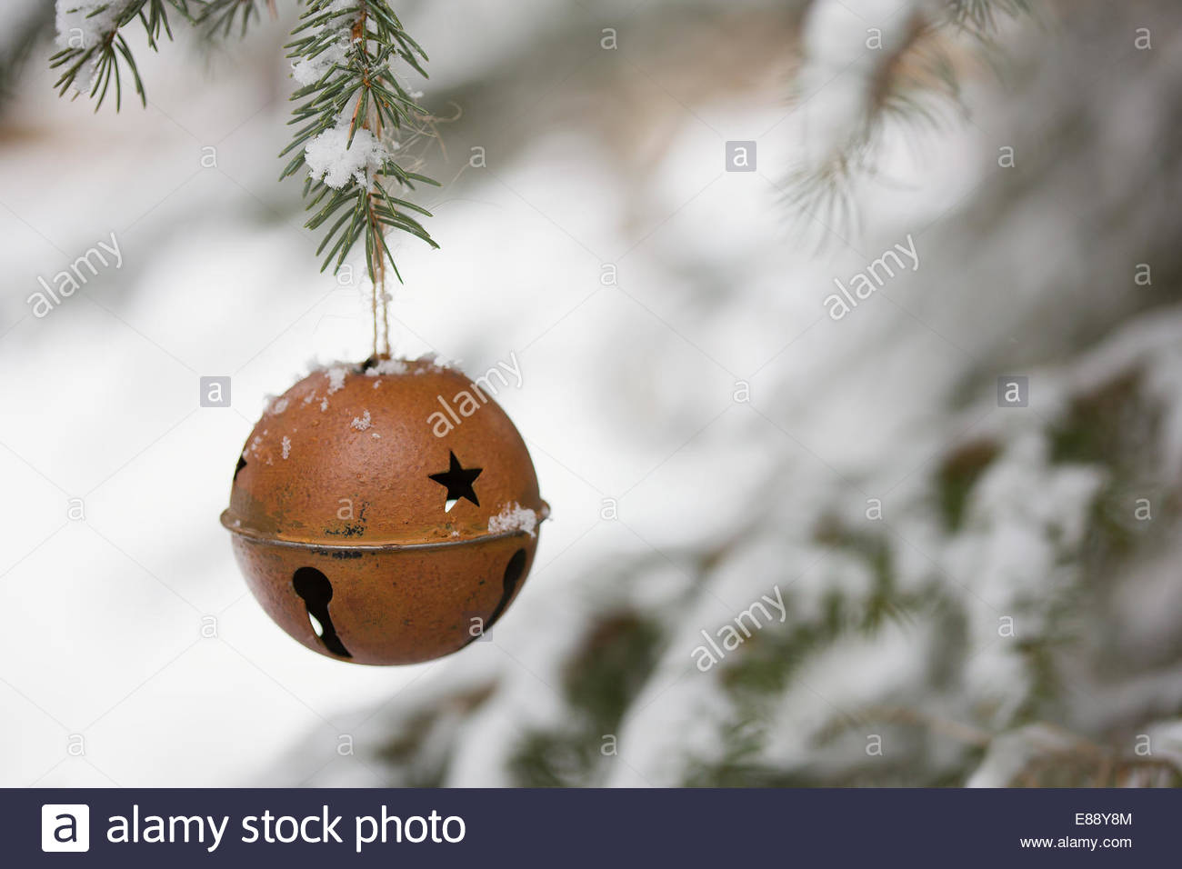 Bell ornament hanging from snowy tree branch - Stock Image
