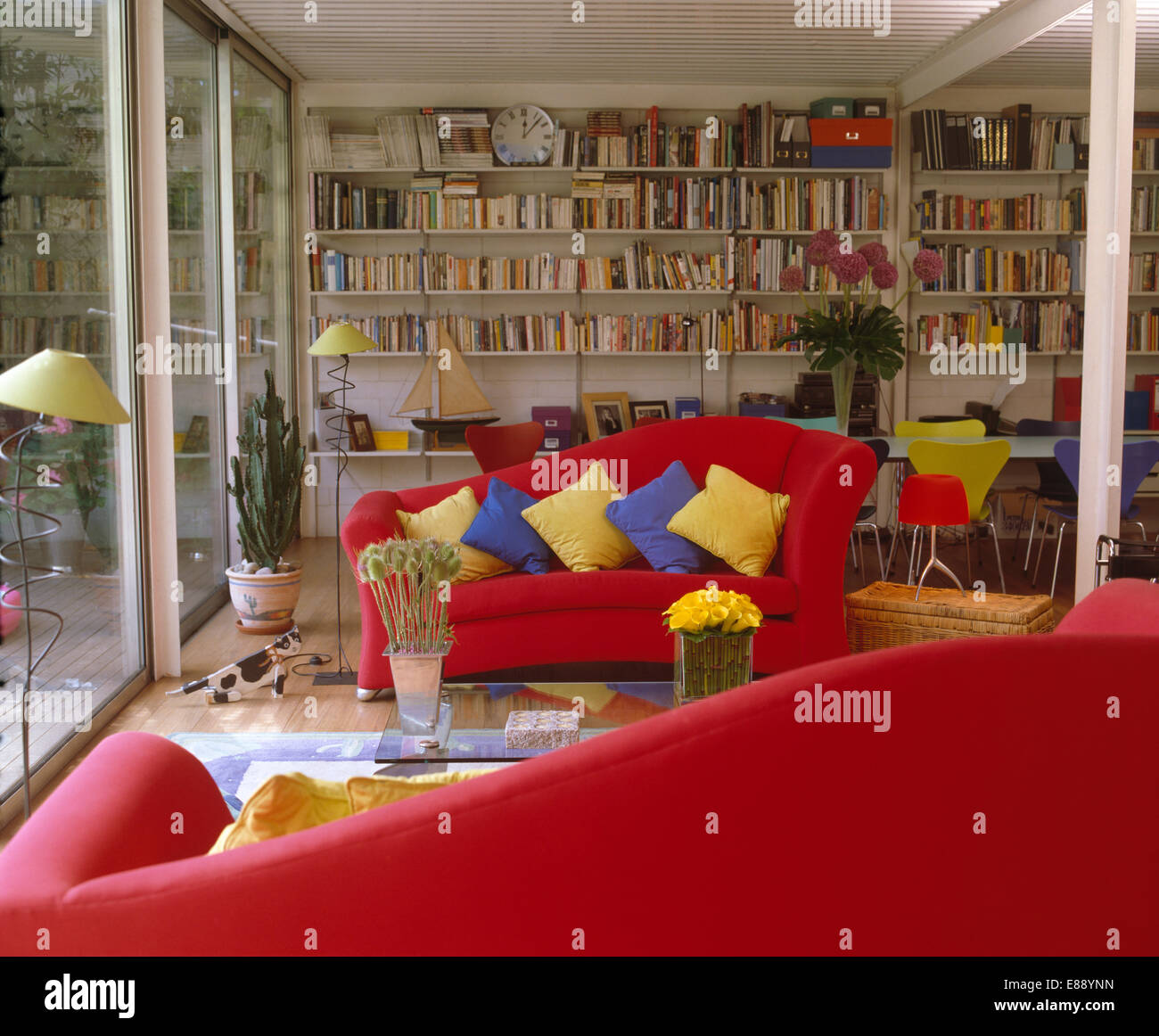Yellow And Blue Cushions On Bright Red Sofas In Modern City Living Room With Bookshelves Covering The Back Wall