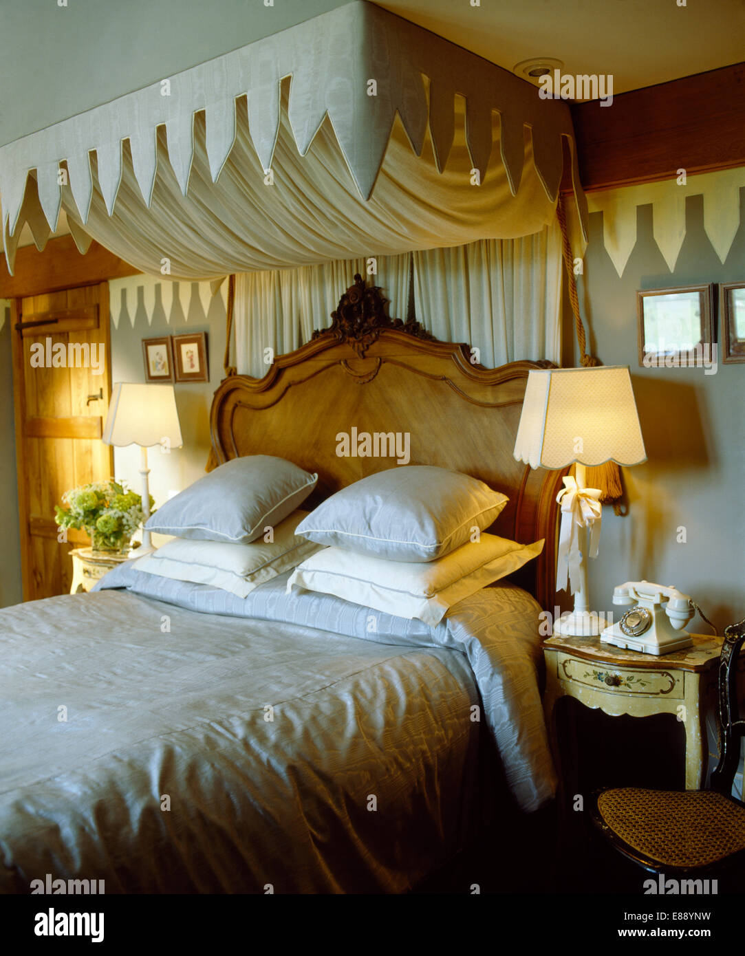 Cream canopy and drapes above antique wood bed piled with cushions in country bedroom with lighted l&s & Cream canopy and drapes above antique wood bed piled with cushions ...