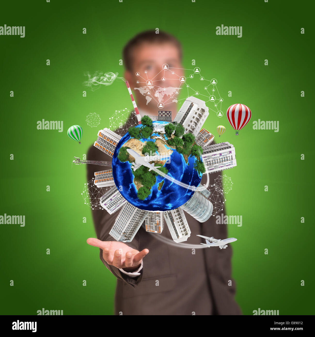 Businessman holding earth with buildings - Stock Image
