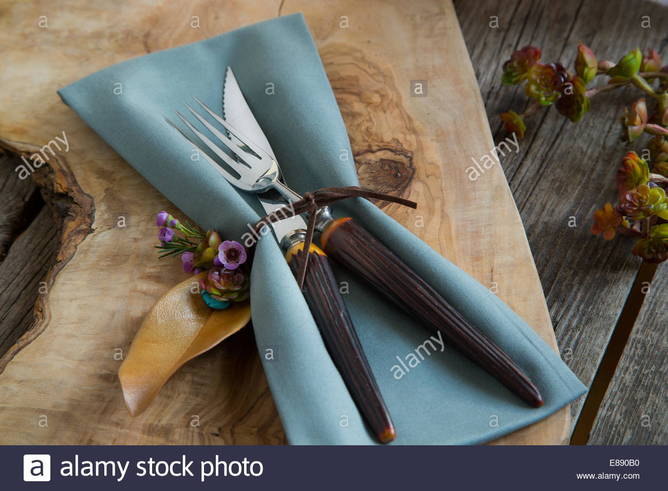 Tied napkin and silverware on wooden cutting board - Stock Image