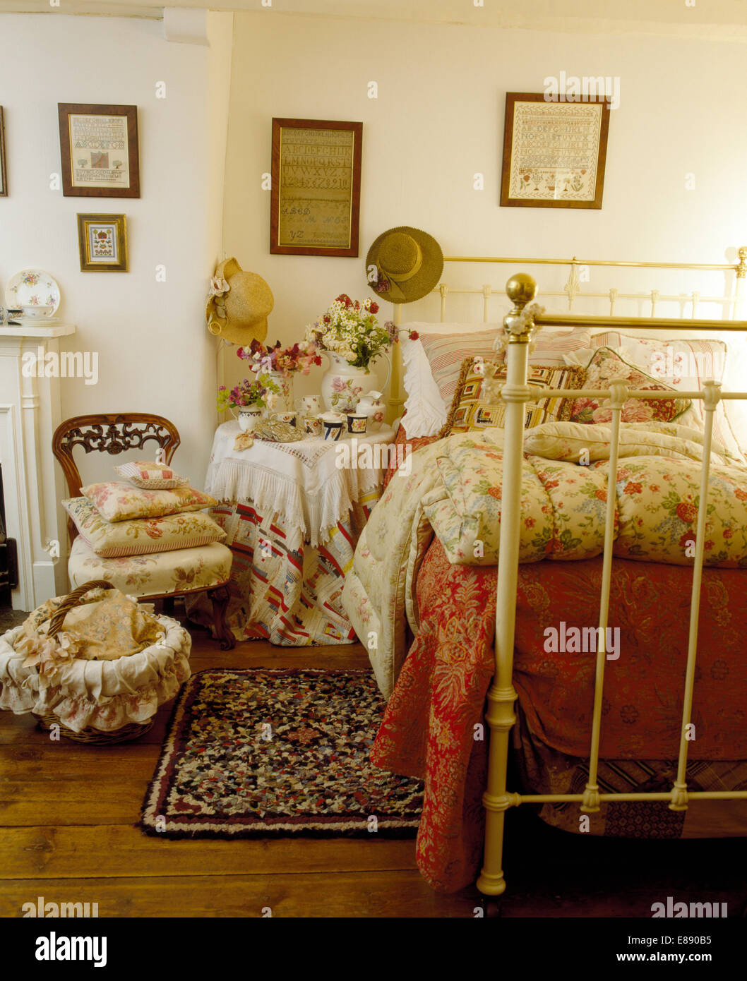 Cottage Bedroom With Floral Quilt On White Wrought Iron Bed And Small Victorian  Chair Piled With Floral Cushions