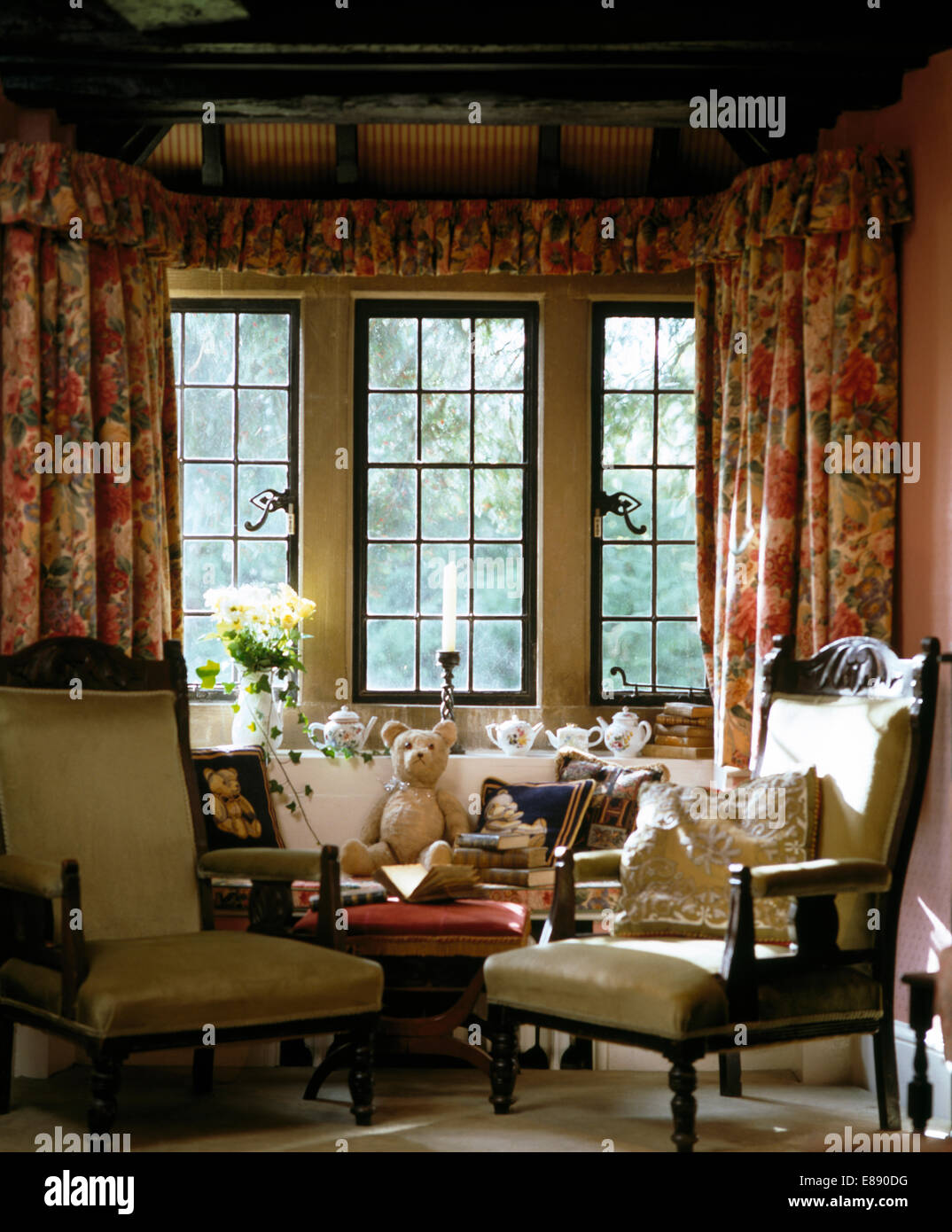 White, wood framed chairs in front of casement window with floral curtains in country bedroom - Stock Image