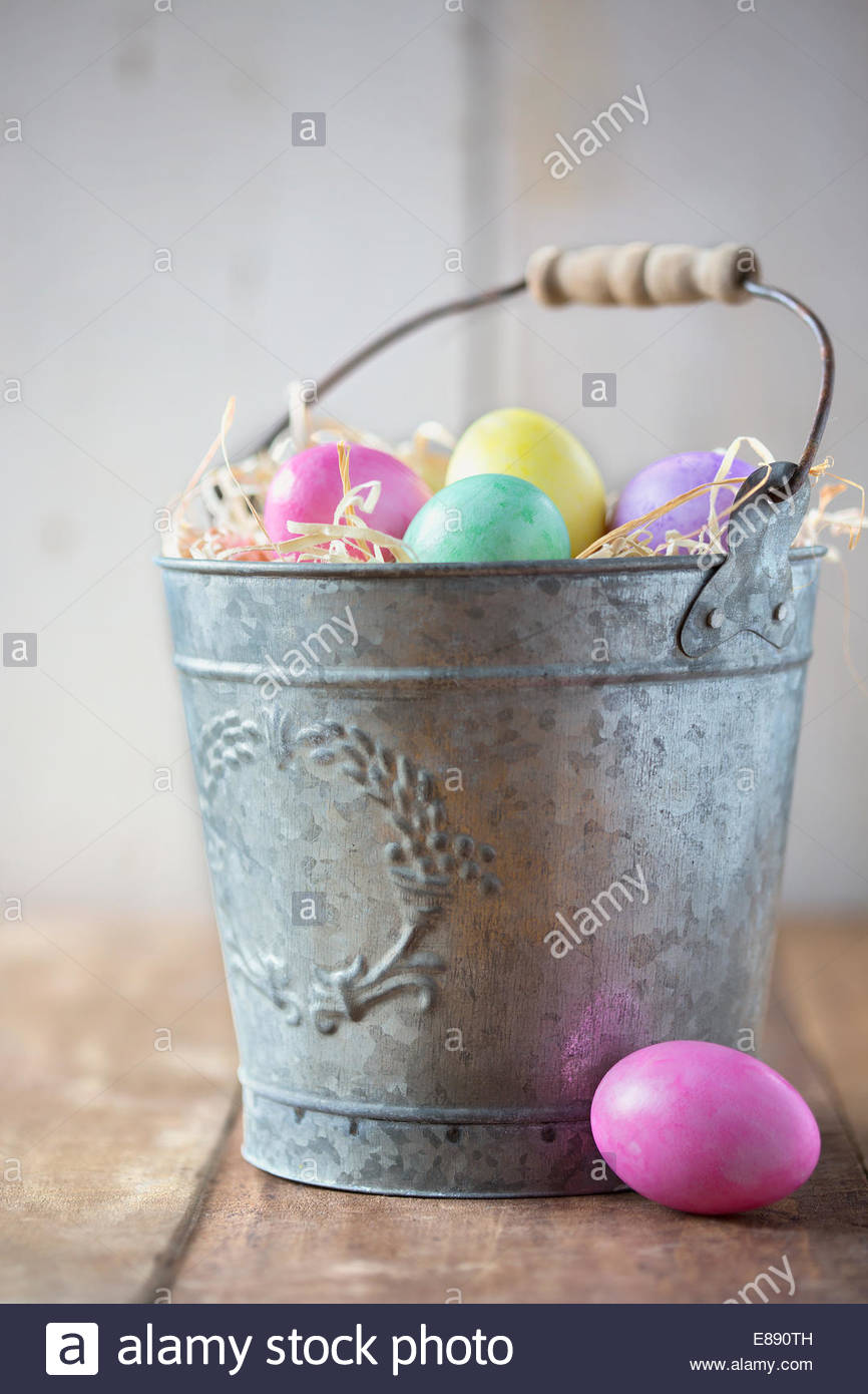 Multicolor Easter eggs in galvanized bucket - Stock Image