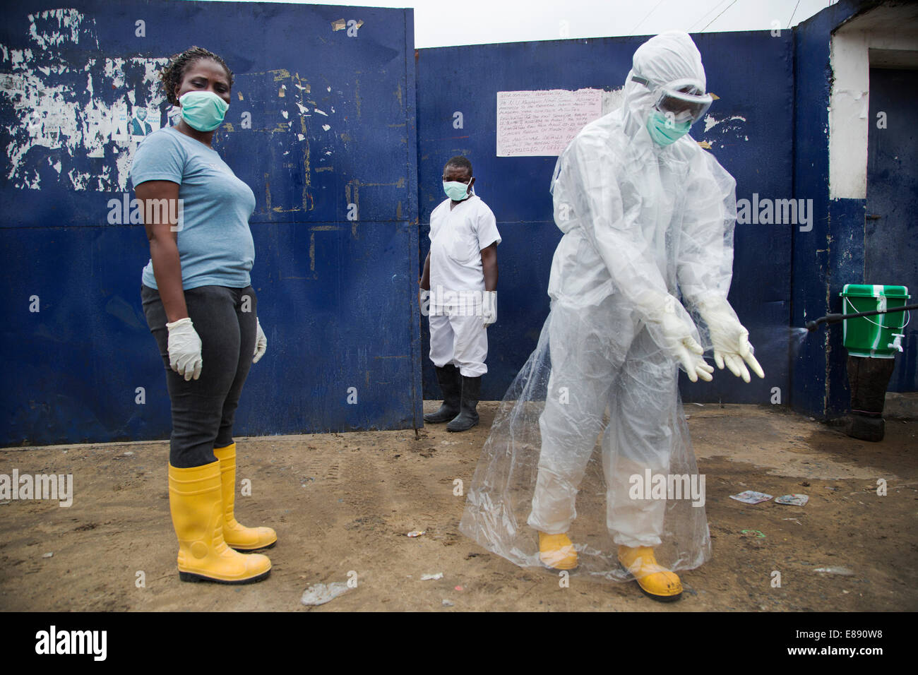 Three people represent different levels of PPE in West Point. West Point is a district of Monrovia Liberia quarantined - Stock Image