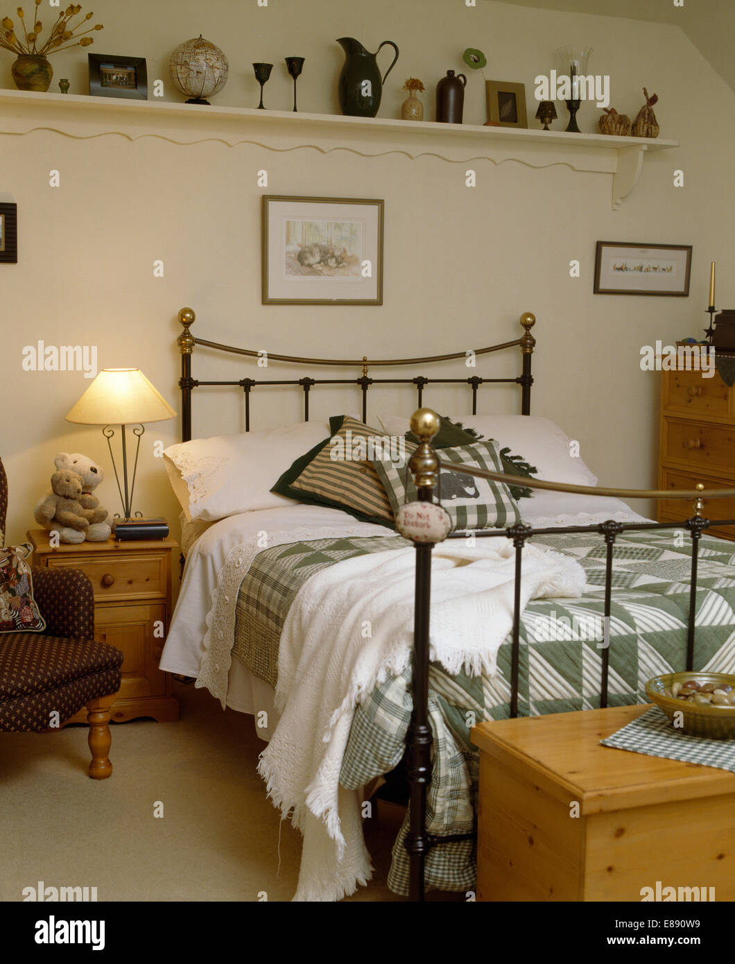Collection of artefacts on white shelf above antique brass bed with green+white quilt in country bedroom - Stock Image