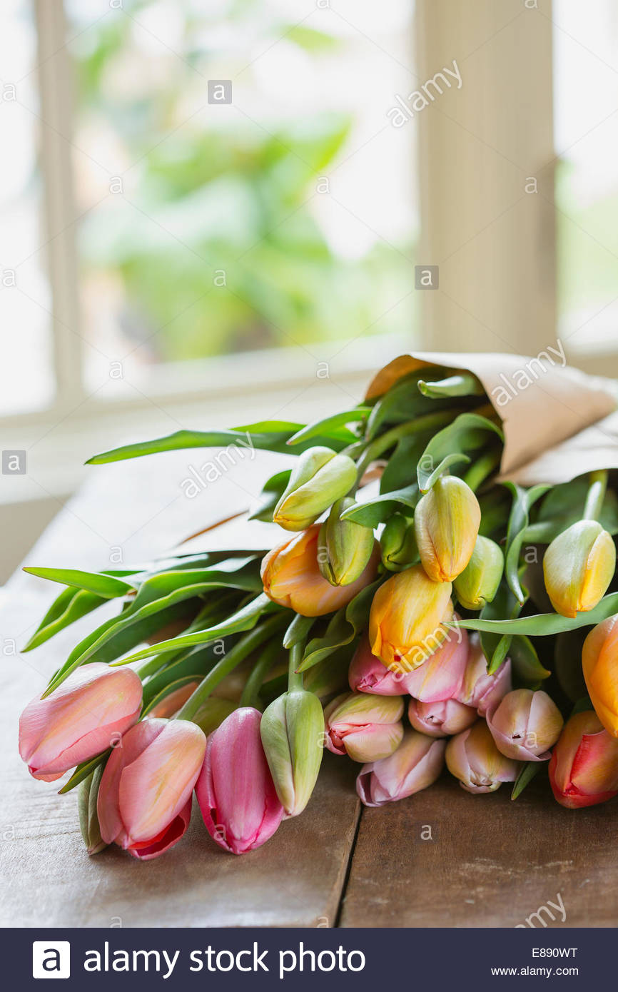 Multicolor tulip bunches wrapped in craft paper - Stock Image
