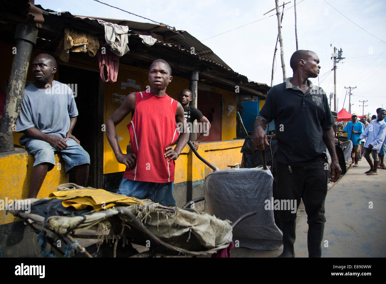 Residents of West Point wait outside a holding clinic. West Point is a district of Monrovia Liberia quarantined - Stock Image