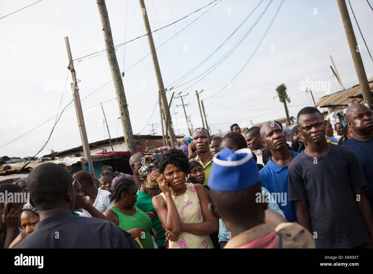 West Point residents wait at the edge of the quarantine. West Point is a district of Monrovia Liberia quarantined - Stock Image