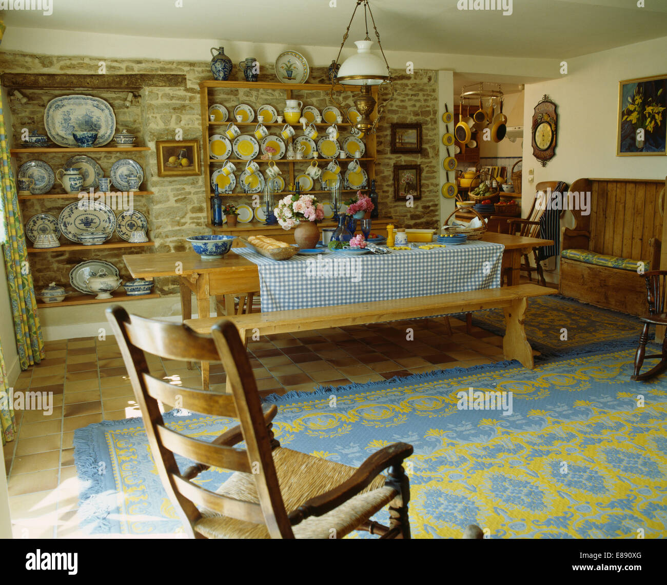 Rocking Chair And Blue+yellow Rug In French Country Dining Room With Bench  At Table With Blue Checked Cloth