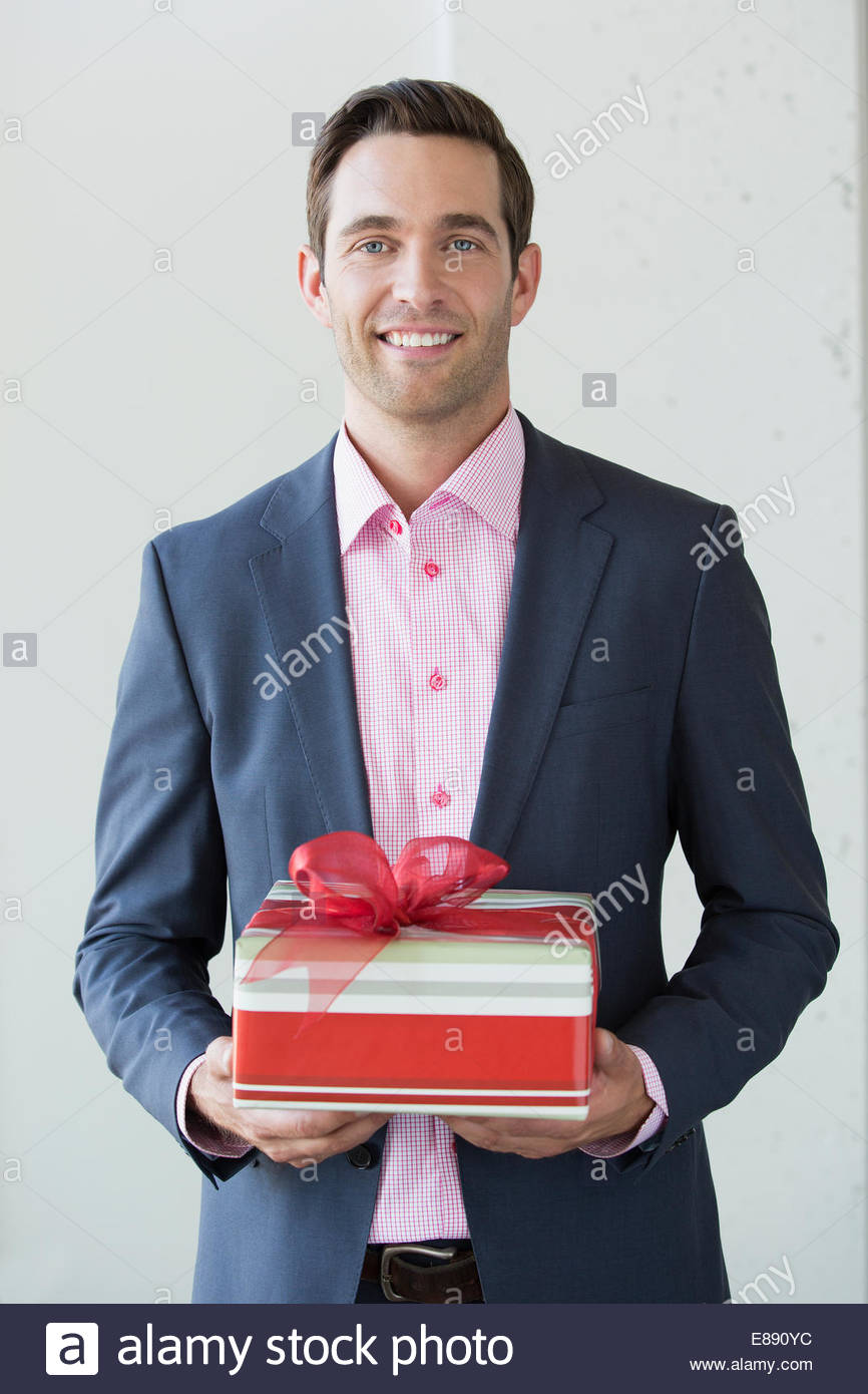 Portrait of well-dressed man holding Christmas gift - Stock Image
