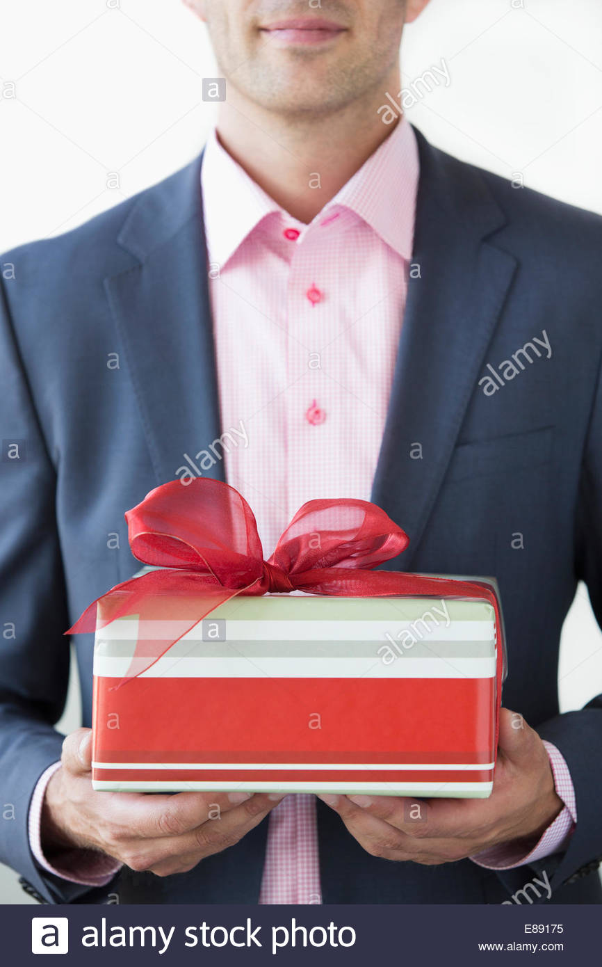 Well-dressed man holding Christmas gift - Stock Image