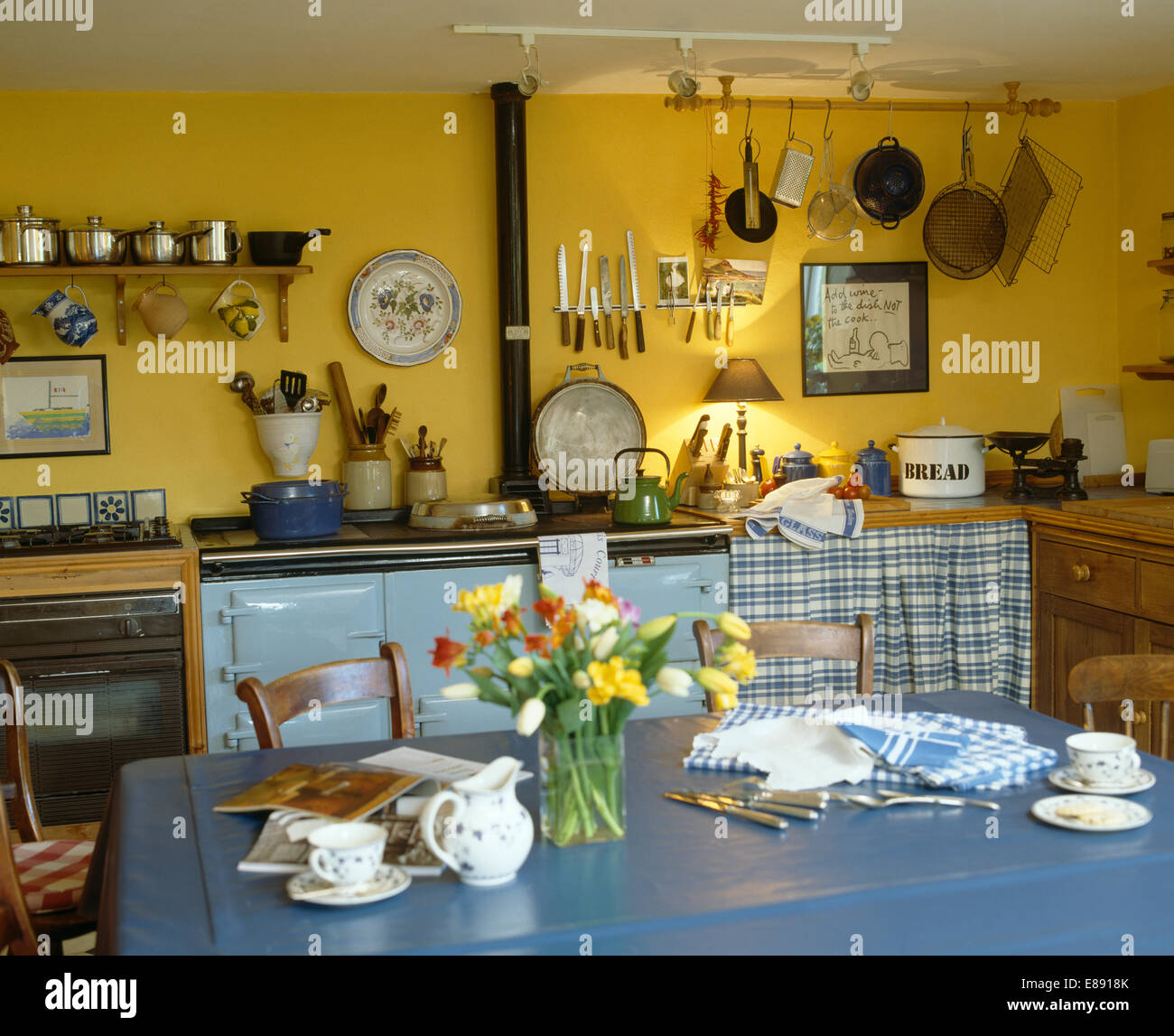 Blue plastic cloth on table in yellow country kitchen with pastel ...