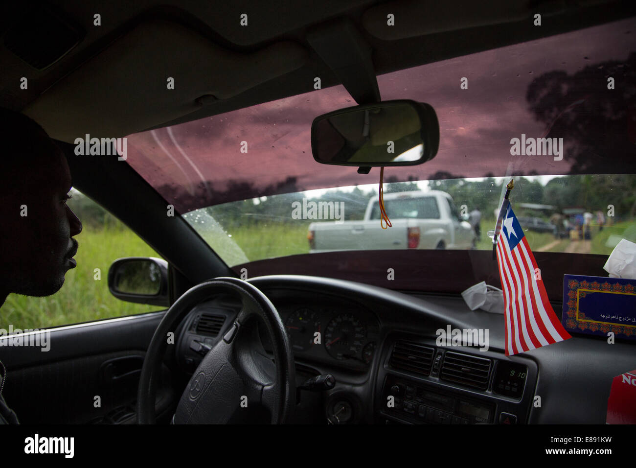 Liberian flag stands strong inside the car before going to the grave of the Ebola victims from Unification Town, - Stock Image