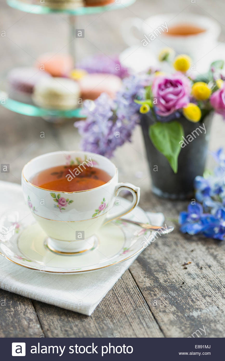 Spring bouquet among teacups and macarons on table - Stock Image