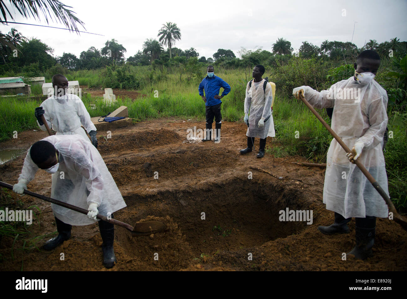 Burial team works to bury another victim of Ebola. Unification Town, Liberia. Aug 30, 2014 - Stock Image