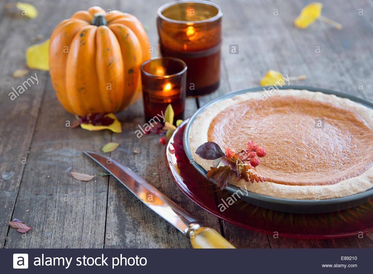 Pumpkin decoration with candles next to pumpkin pie - Stock Image