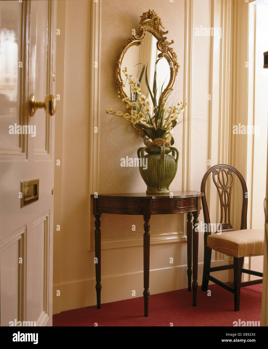 Antique Mirror Above Console Table With Gladioli In Large Green Pot In  Panelled Hall