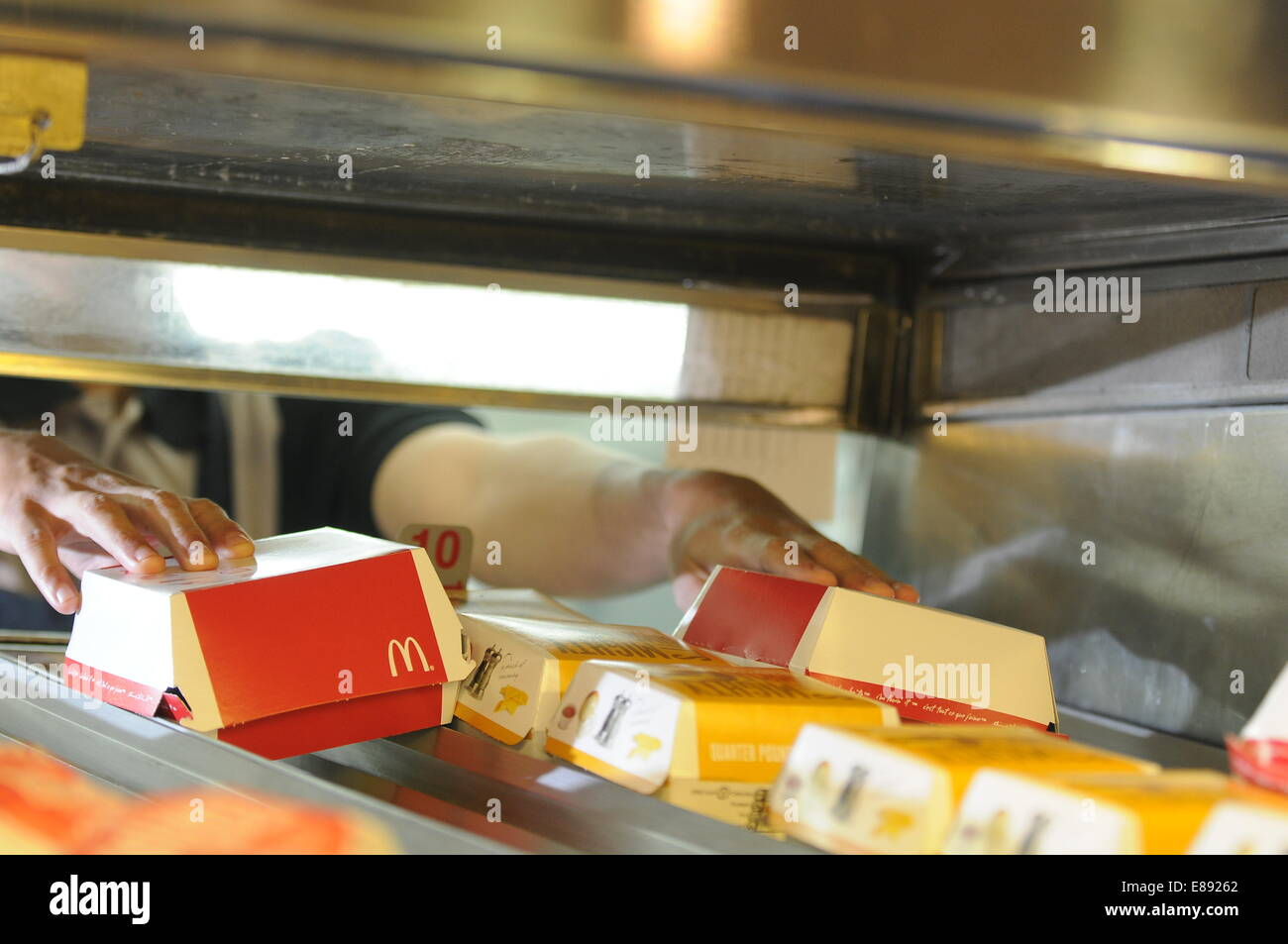 McDonald's worker employee working at a McDonald's fast food restaurant. - Stock Image