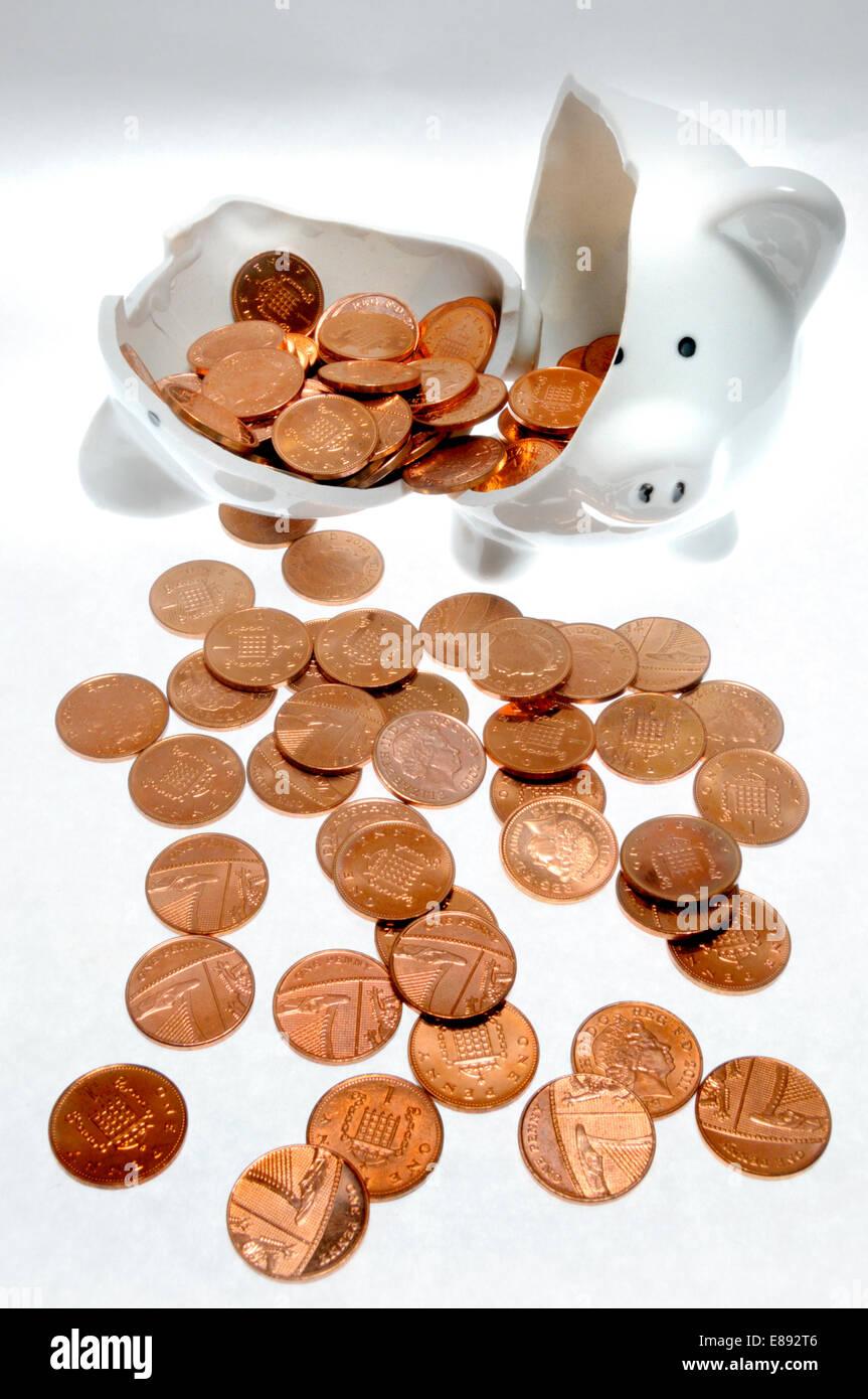 Broken piggy bank and pennies - Stock Image