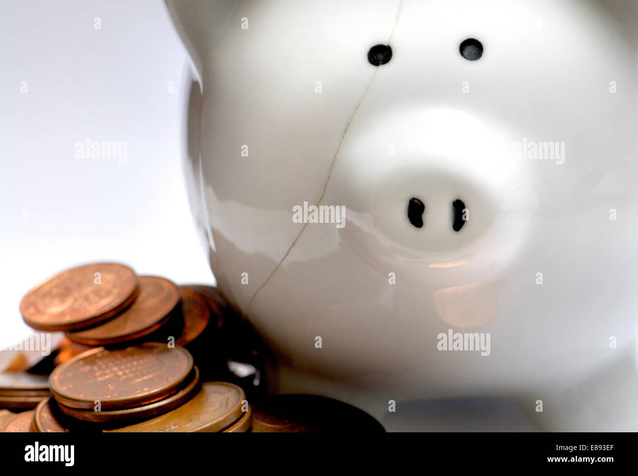 Cracked piggy bank and pennies Stock Photo