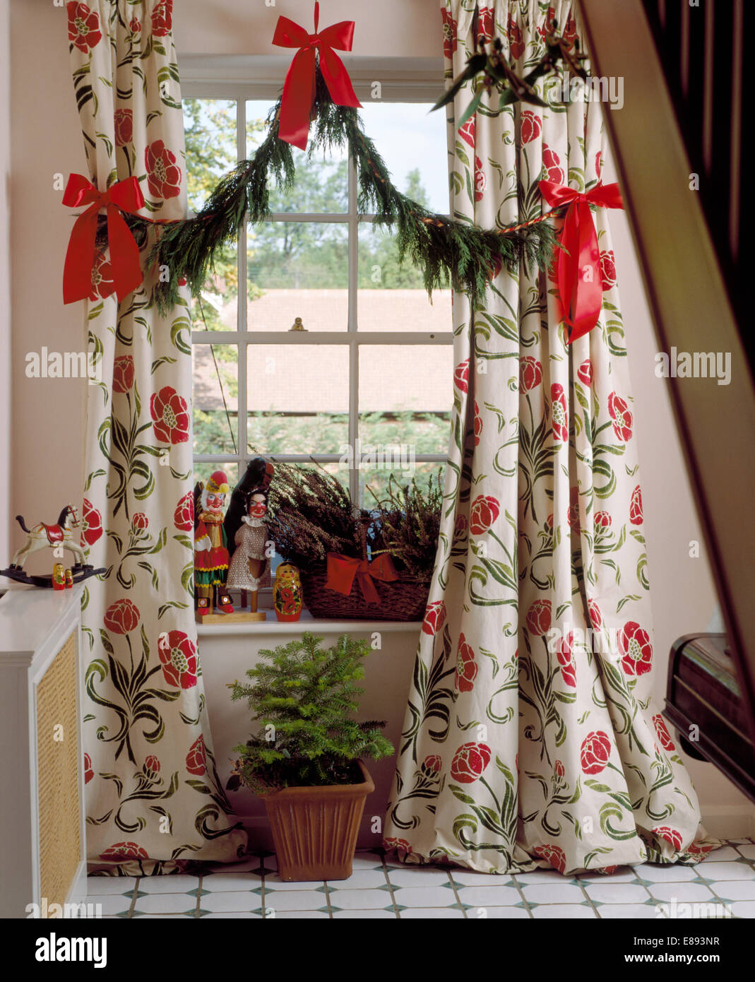 Red ribbons decorating simple conifer garland between ...