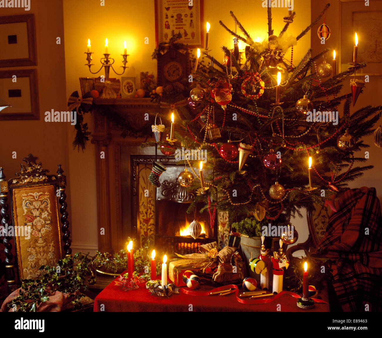 lighted candles on christmas tree and on small table beside fireplace in cottage living room