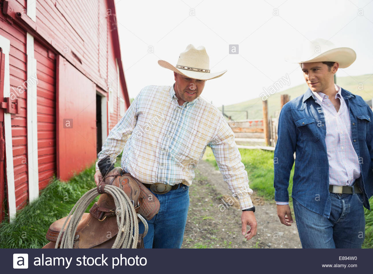 Ranchers carrying saddle and tack outside barn - Stock Image