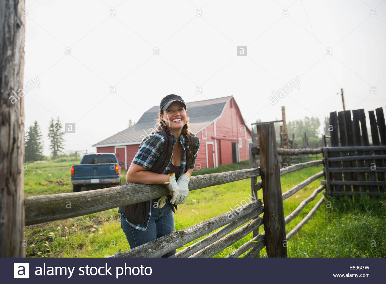 Smiling rancher leaning on pasture fence - Stock Image