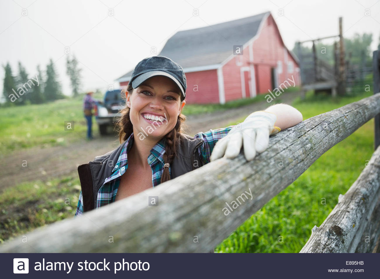 Portrait of smiling rancher leaning on fence post - Stock Image