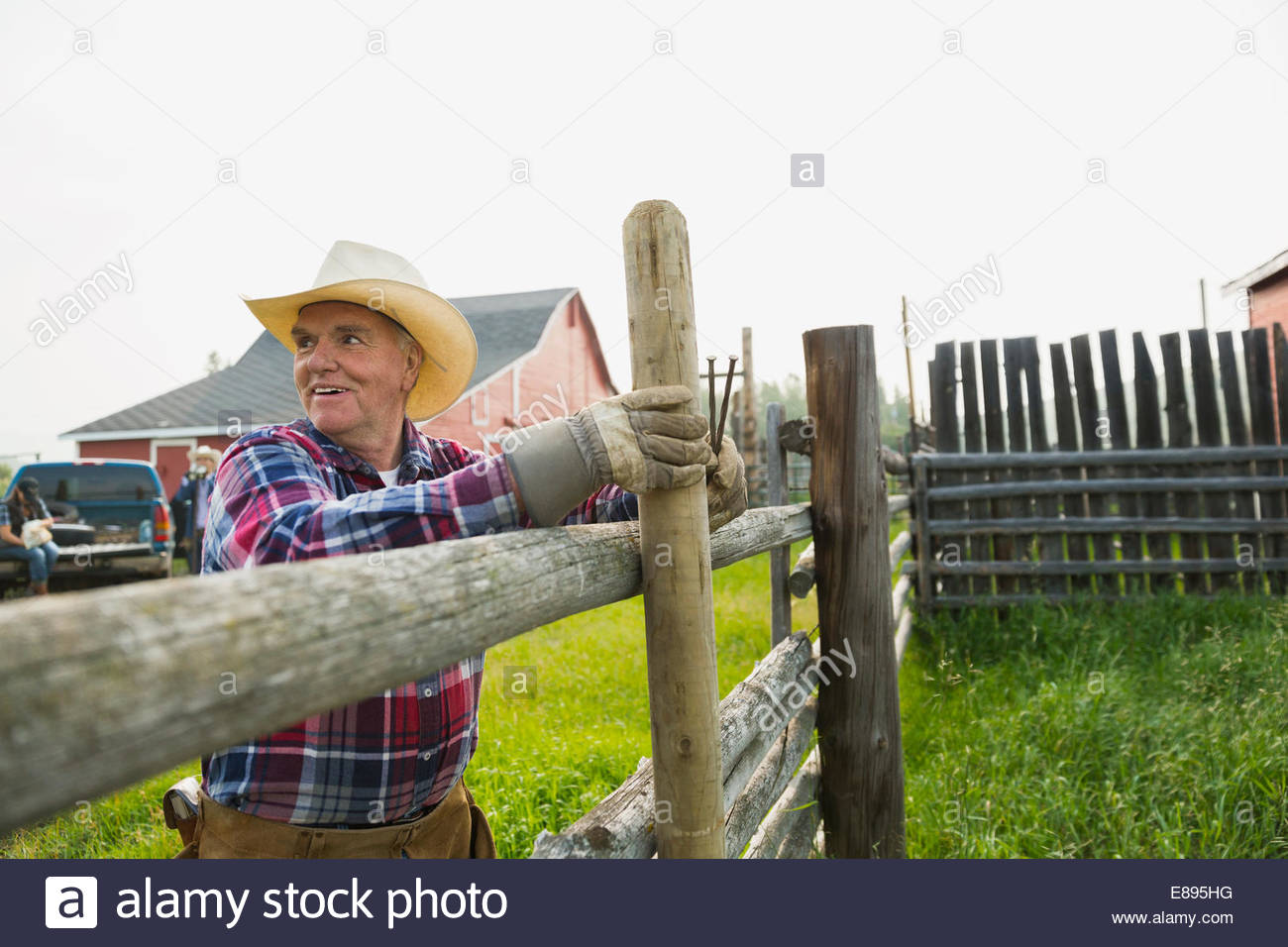 Rancher fixing fence post in pasture - Stock Image